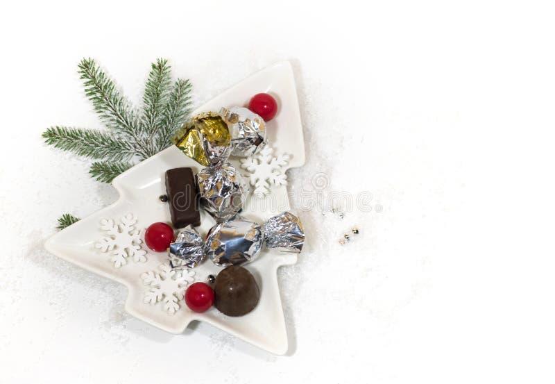 Ano novo, cartão do feriado do Natal Chocolate da árvore de Natal do prato cerâmico, doces de prata imagem de stock