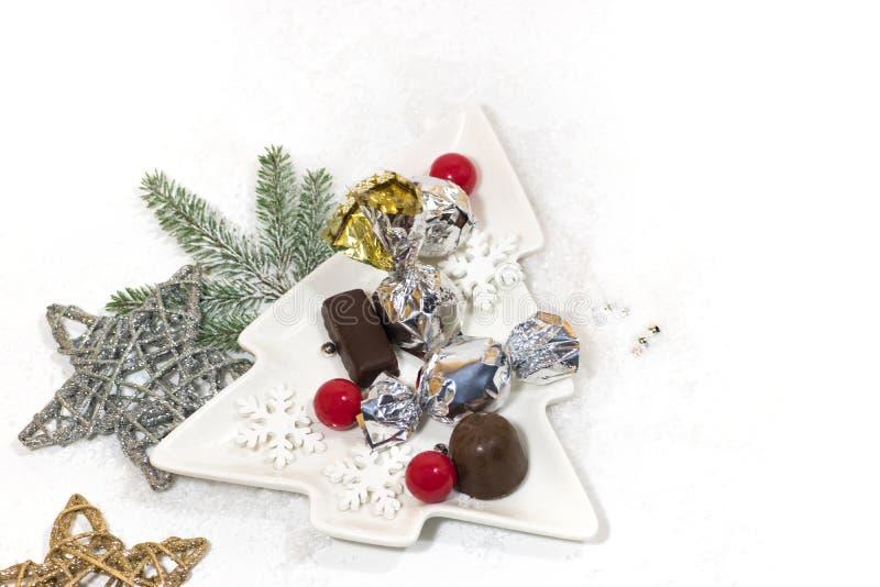 Ano novo, cartão do feriado do Natal Chocolate da árvore de Natal do prato cerâmico, doces de prata fotografia de stock royalty free