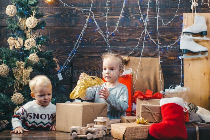Ano novo da criança Natal das crianças Crianças que jogam com presente Véspera do ` s do ano novo Caixa de presente do Natal e fa imagem de stock
