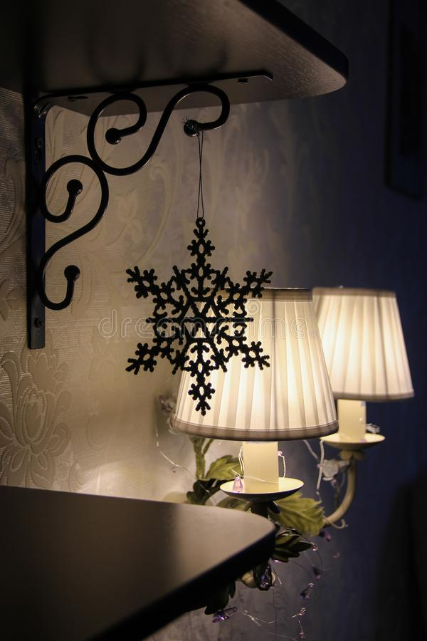Ano novo do Natal interior acolhedor da sala escura com a lâmpada de parede e o brinquedo pequenos do floco de neve no close up d foto de stock royalty free