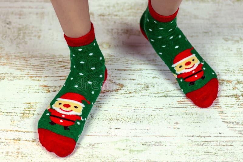 Ano novo e Feliz Natal Feriado feliz Pés do bebê em peúgas vermelhas e verdes com Santa Claus fotografia de stock royalty free