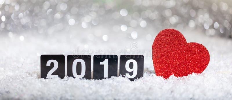 Ano novo 2019 e um coração vermelho na neve, luzes abstratas do bokeh imagem de stock royalty free