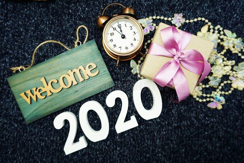 Ano novo feliz 2020 com fundo da decoração do sinal bem-vindo, da caixa de presente e do despertador imagens de stock