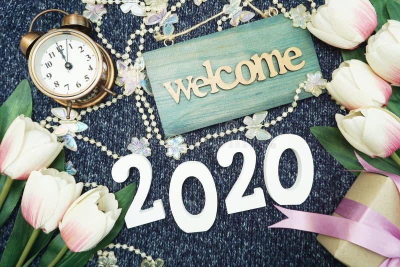Ano novo feliz 2020 com fundo da decoração do sinal bem-vindo, da caixa de presente e do despertador foto de stock royalty free