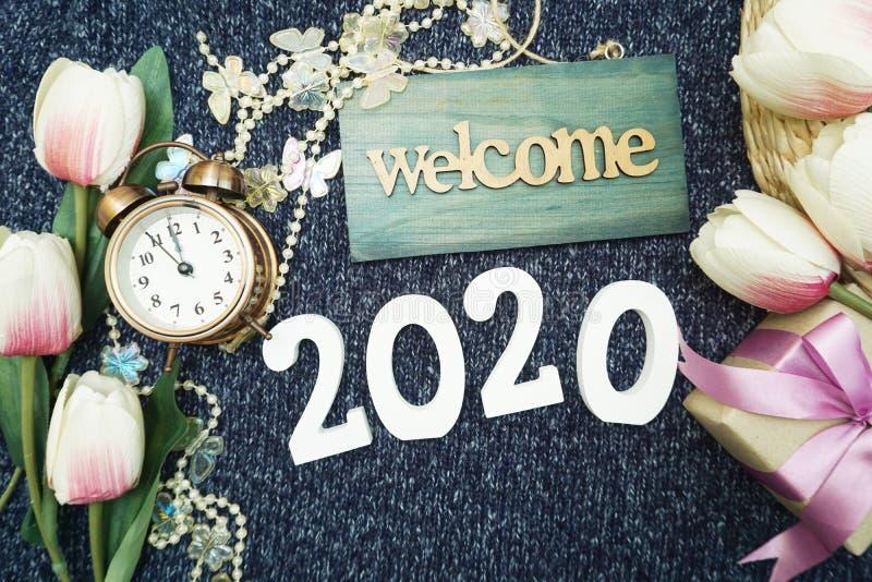 Ano novo feliz 2020 com fundo da decoração do sinal bem-vindo, da caixa de presente e do despertador fotos de stock royalty free