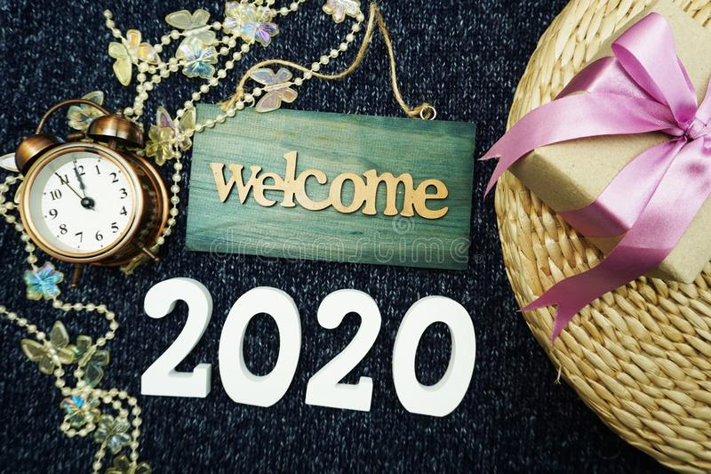 Ano novo feliz 2020 com fundo da decoração do sinal bem-vindo, da caixa de presente e do despertador imagem de stock