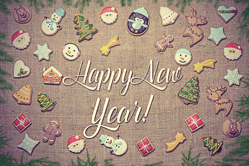 Ano novo feliz! Escrito entre cookies do pão-de-espécie e ramos do abeto fotos de stock