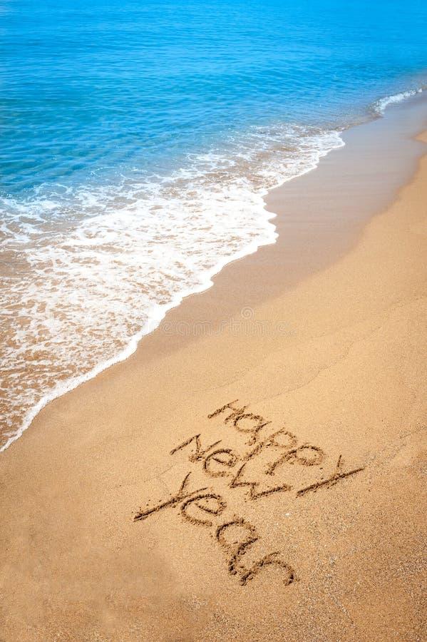 Ano novo feliz escrito na areia na praia tropical fotos de stock