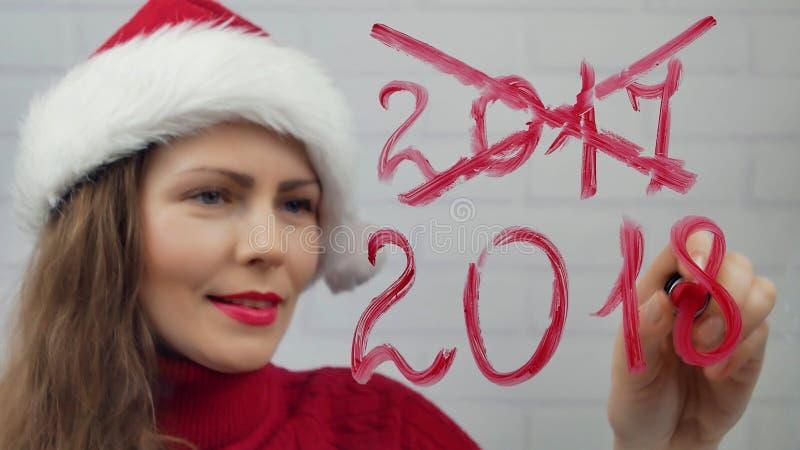 Ano novo feliz A menina de Santa escreve o batom no ano novo feliz das palavras de vidro Menina bonita no chapéu que envia uma me fotografia de stock