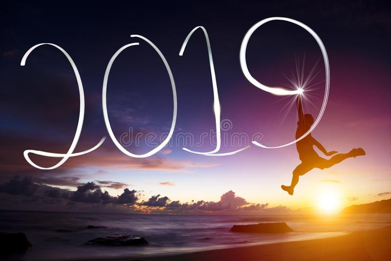 Ano novo 2019 o homem que salta e que tira na praia fotos de stock royalty free