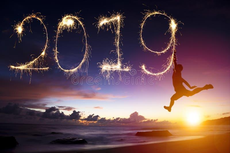 Ano novo 2019 o homem que salta e que tira na praia imagens de stock