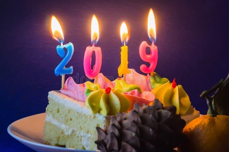 Ano novo 2019 Velas de queimadura do feriado no bolo e na colisão Close-up fotos de stock