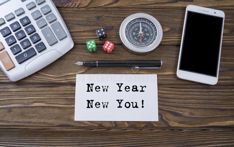 Ano novo novo você escrito no papel, na mesa de madeira do fundo com calculadora, nos dados, no compasso, no telefone esperto e n imagem de stock
