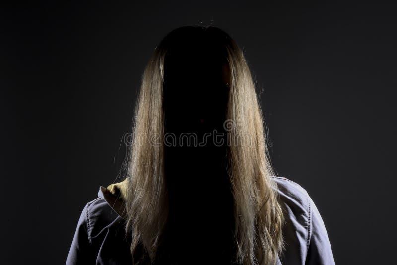 Anoniem blonde in schaduw en vrees stock fotografie