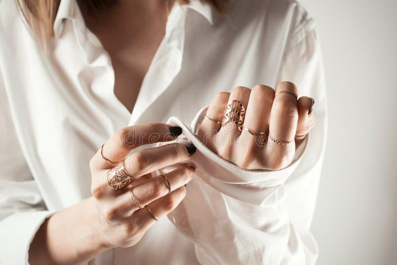 Anoniem close-upportret van witte vrouw die haar wit overhemd dichtknopen stock fotografie