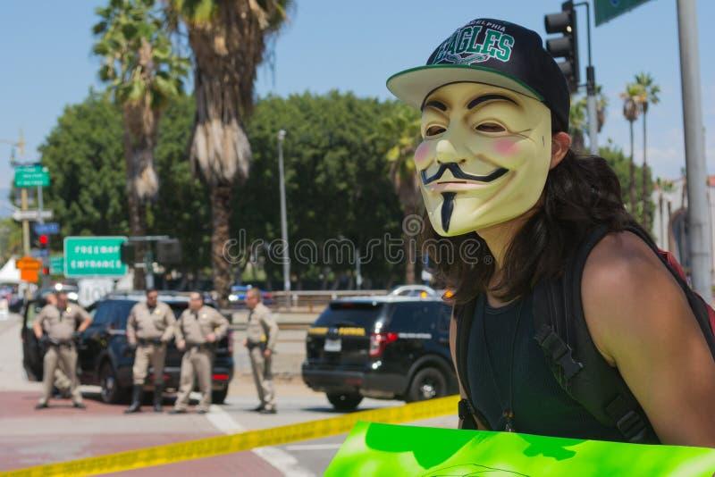 Anoniem met mascara met politie op de achtergrond stock afbeelding