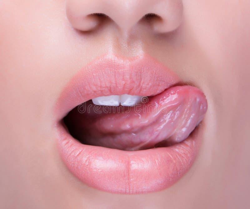 Anoniem schot van een open mond met tong die sappige lippen likken stock foto's