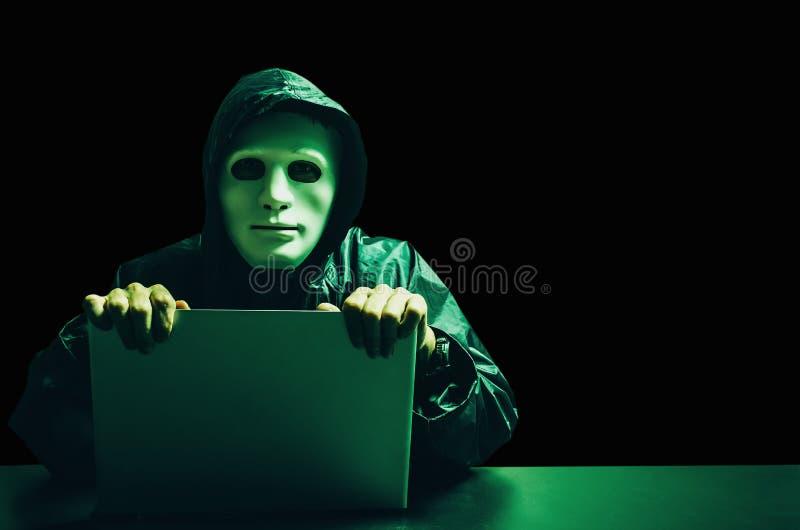 Anonieme computerhakker in wit masker en hoodie Verduisterd donker gezicht Gegevensdief, Internet-aanval, darknet en cyber veilig stock afbeelding
