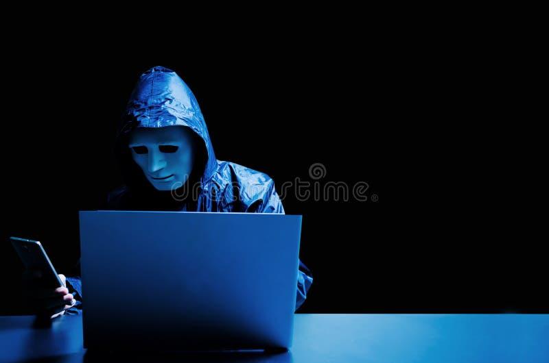 Anonieme computerhakker in wit masker en hoodie Verduisterde donkere gezichts aanvallende mensen door een smartphone royalty-vrije stock fotografie
