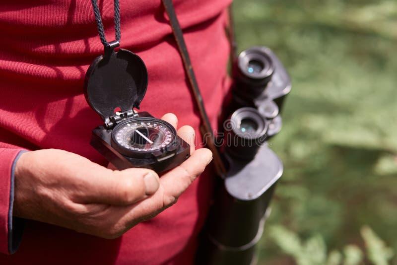 Anonieme foto van man hand met kompas, reiziger op houten achtergrond die rood toevallig overhemd dragen, die met verrekijkers st royalty-vrije stock foto