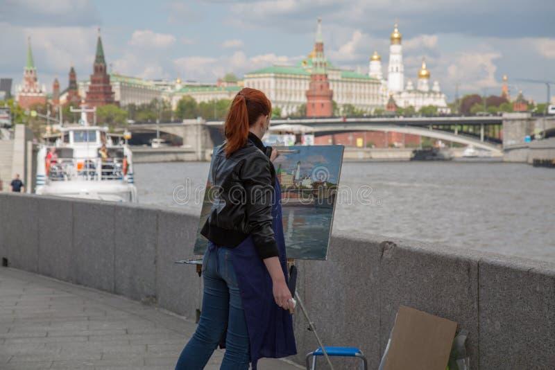 Anonieme jonge vrouwelijke schilderende kunstenaar bij het landschap van Moskou van de het werk plein lucht royalty-vrije stock foto's