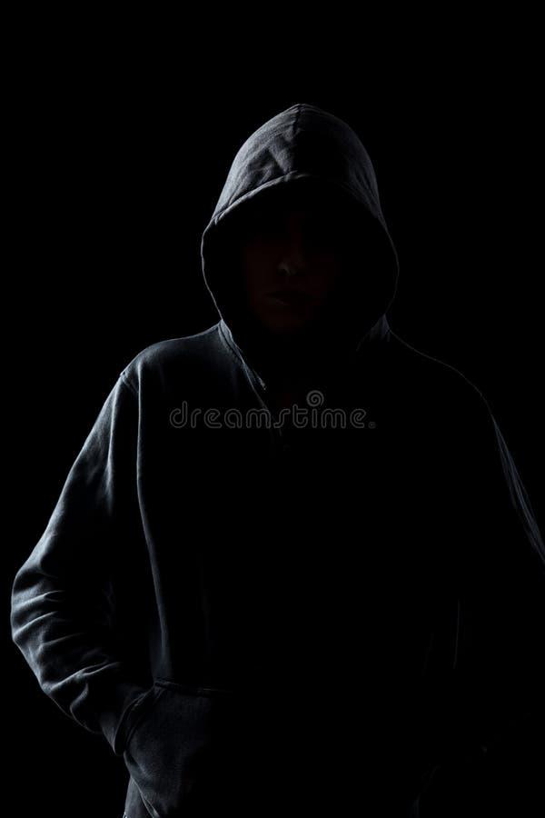 Anonieme kerel in hoodie in de duisternis royalty-vrije stock afbeelding