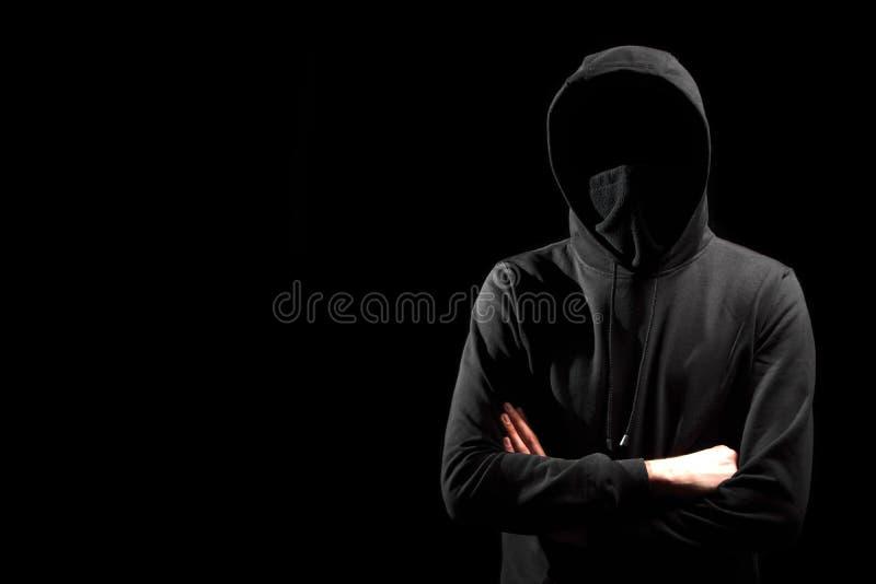 Anonieme mens in hoodie die zich op zwarte bevinden stock afbeelding