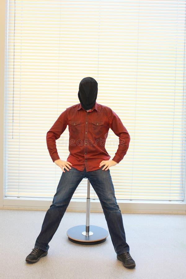 Anonieme mens in zwarte zak op hoofdzitting op pneumatische kruk stock afbeelding