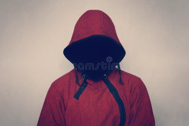 Anonieme onbekende en onherkenbare mens die zonder identiteit kap in donkere ruimte, griezelige misdadige persoon draagt stock afbeelding