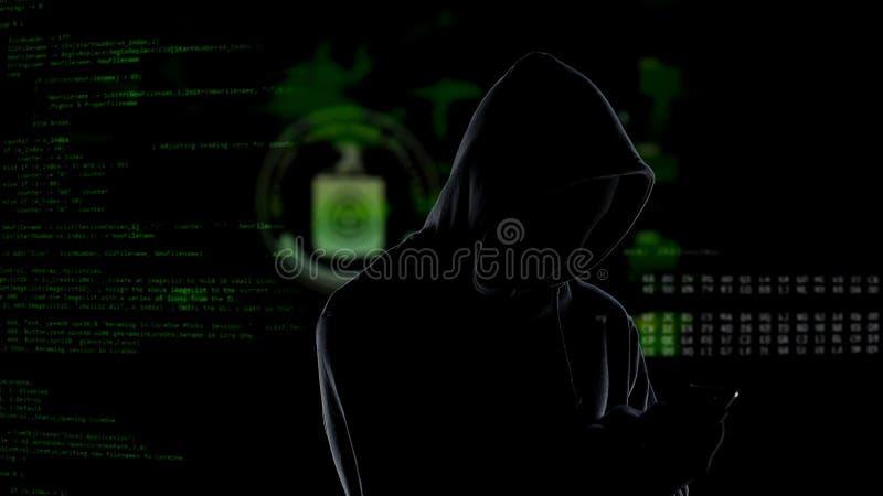 Anonieme onherkenbare hakker die met een kap smartphone gebruiken om gegevens te stelen, cybercrime stock afbeelding
