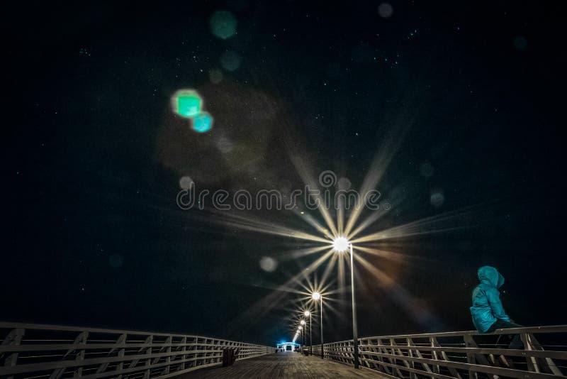 Anonieme persoonszitting op traliewerk op brug bij nacht stock afbeelding