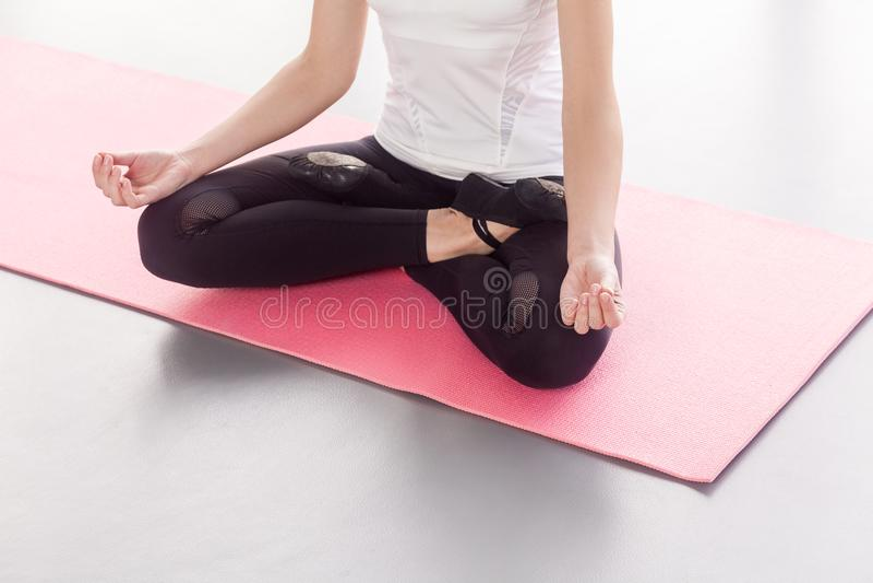 Anonieme vrouwenzitting in lotusbloemhouding, die yoga doen royalty-vrije stock foto