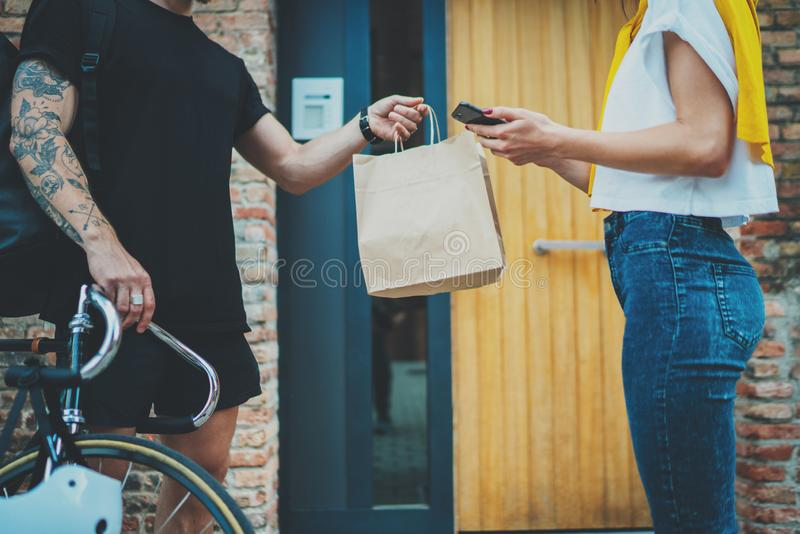 Anonimous bike delivery food service at home. Man courier delivered the order no name bag with food.  stock images