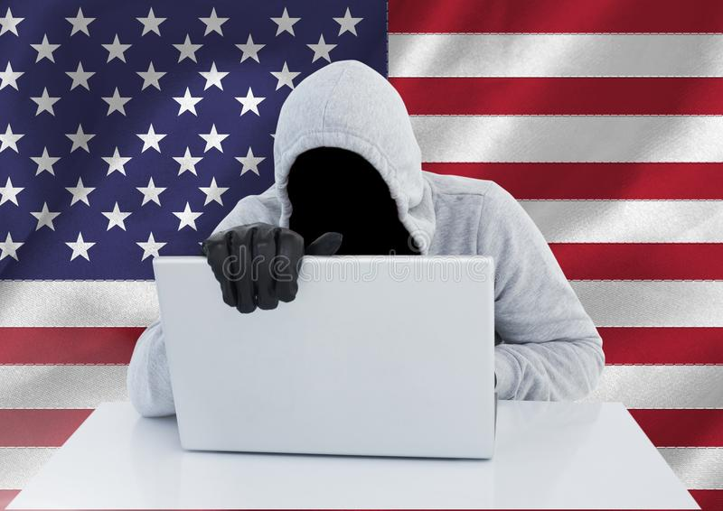 Anonym brottsling i huv med bärbara datorn som är främst av amerikanska flaggan royaltyfria foton