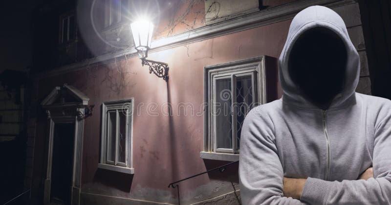 Anonym brottsling i huv på den mörka gatan royaltyfri fotografi