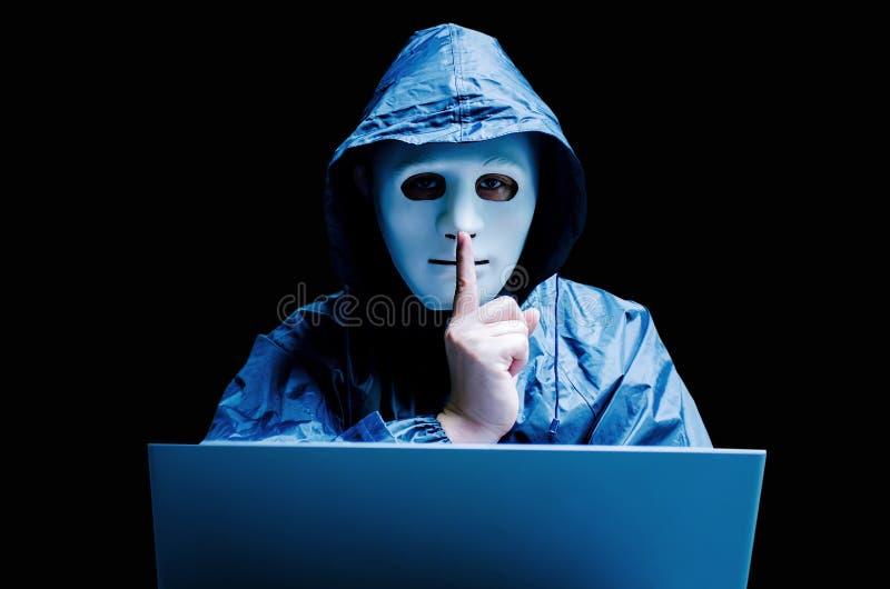 Anonym datoren hacker i den vita maskeringen och hoodien Fördunklad mörk framsida som gör för att tysta gest på mörk bakgrund, arkivfoto