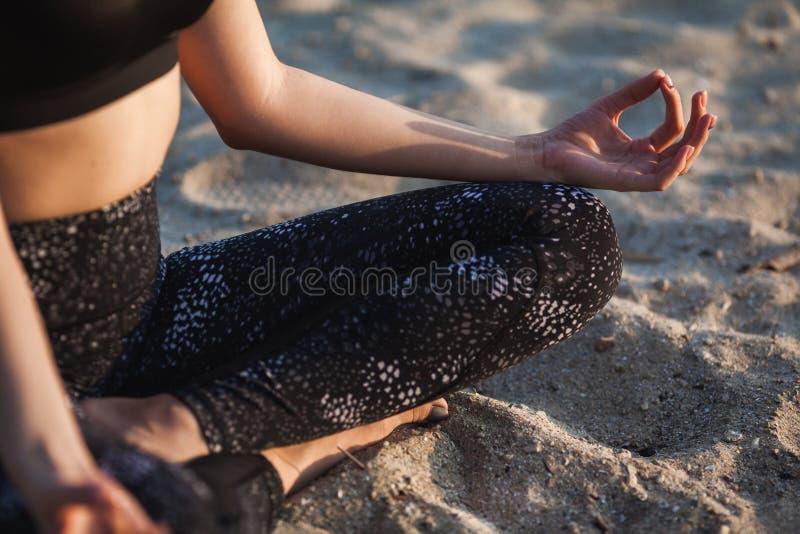 Anonym hand för närbild av kvinnan i Lotus Position At sandstrand arkivfoton