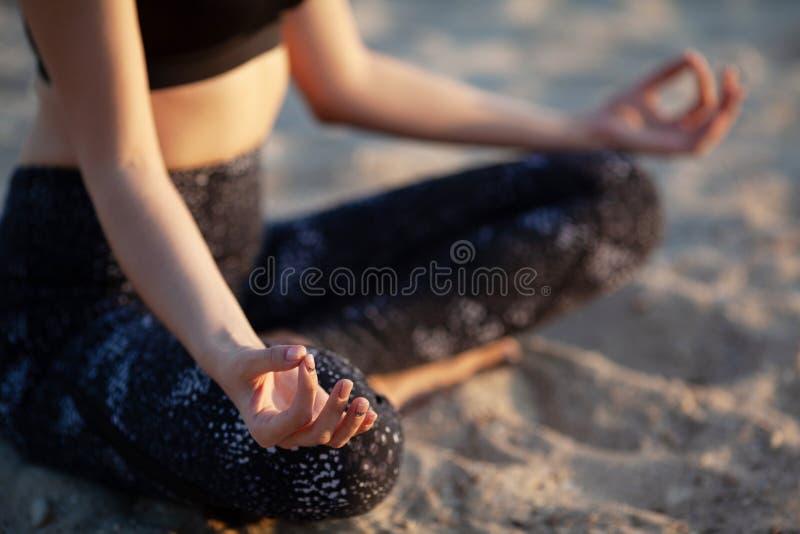 Anonym hand för närbild av kvinnan i Lotus Position At sandstrand arkivfoto