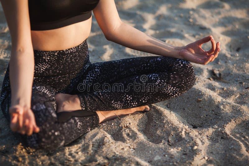 Anonym hand för närbild av kvinnan i Lotus Position At sandstrand royaltyfria bilder