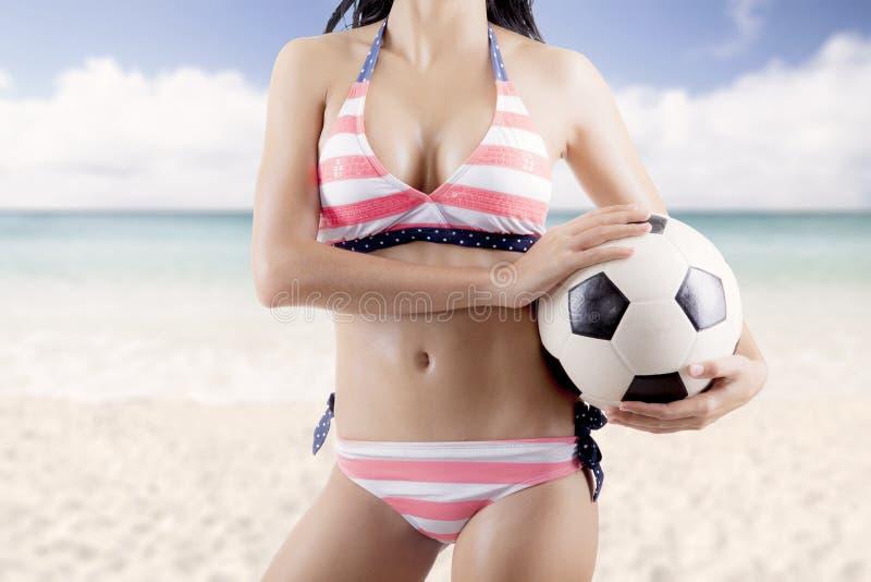 Anonym kvinna med fotbollbollen på stranden royaltyfria bilder