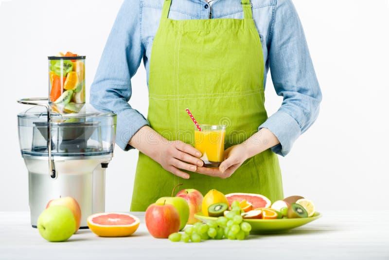 Anonym kvinna som bär ett förkläde, hållande exponeringsglas av nytt pressande fruktsaft, sunt livsstilbegrepp arkivfoton