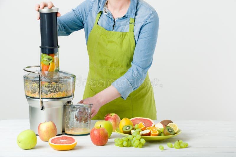 Anonym kvinna som bär ett förkläde som förbereder sund fruktfruktsaft genom att använda den moderna elektriska juiceren, sunt liv royaltyfria foton