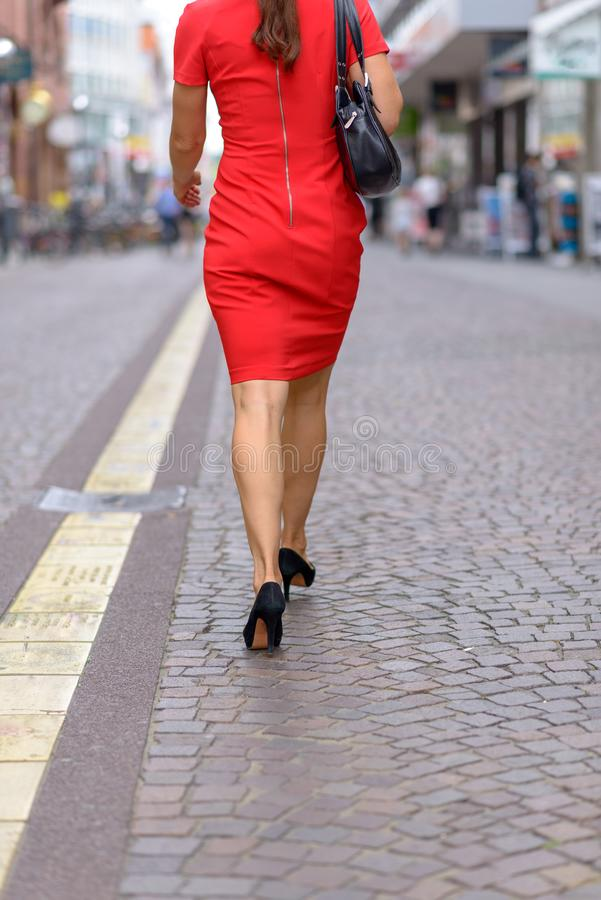 Anonym kvinna som går i mitt av en gata royaltyfri bild