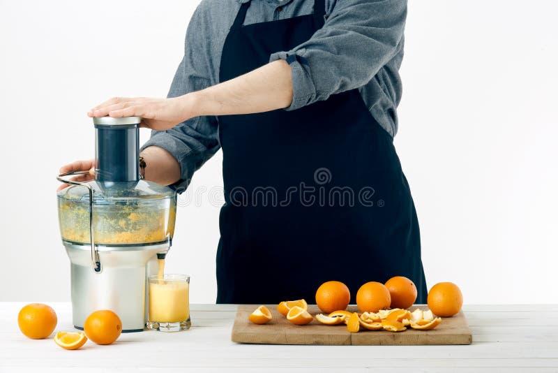 Anonym man som bär ett förkläde och att förbereda sund orange fruktsaft, genom att använda den moderna elektriska juiceren, sunt  royaltyfri fotografi