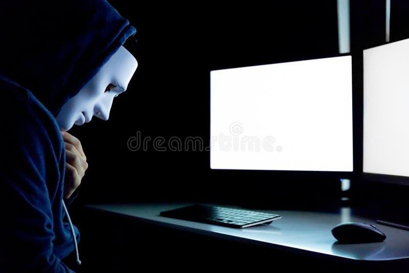 Anonym och maskerad en hacker som använder datoren med den isolerade vita bildskärmskärmen för att sätta in någon text, ord, bild arkivfoto