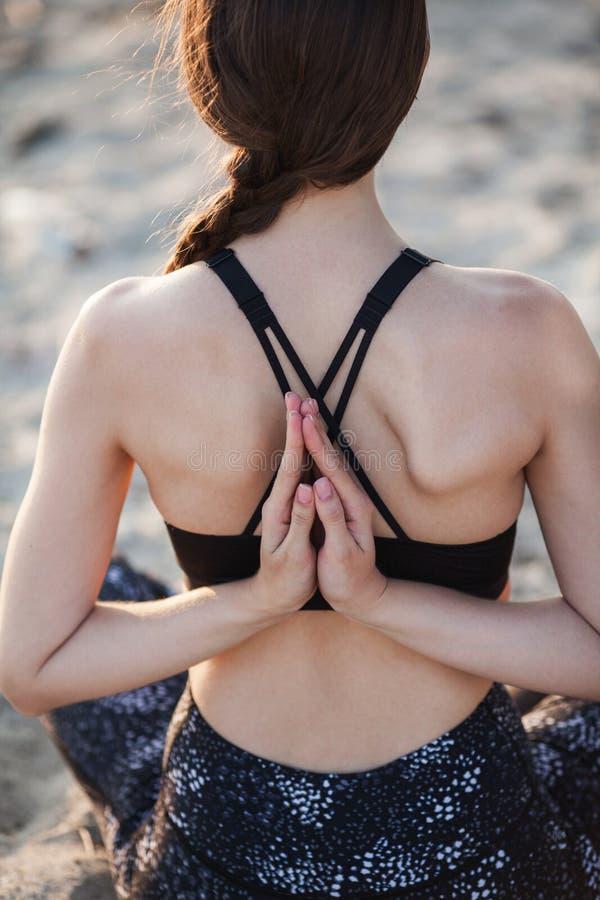 Anonym tillbaka sikt av kvinnan med handen bak övande yoga på sandstranden close upp royaltyfria foton