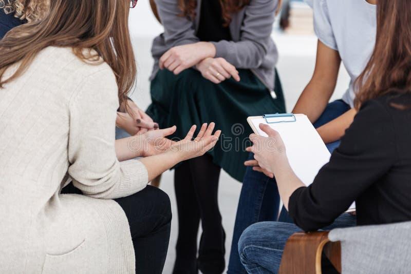 Anonyma kvinnor som sitter i cirkel under gruppm?te arkivfoton