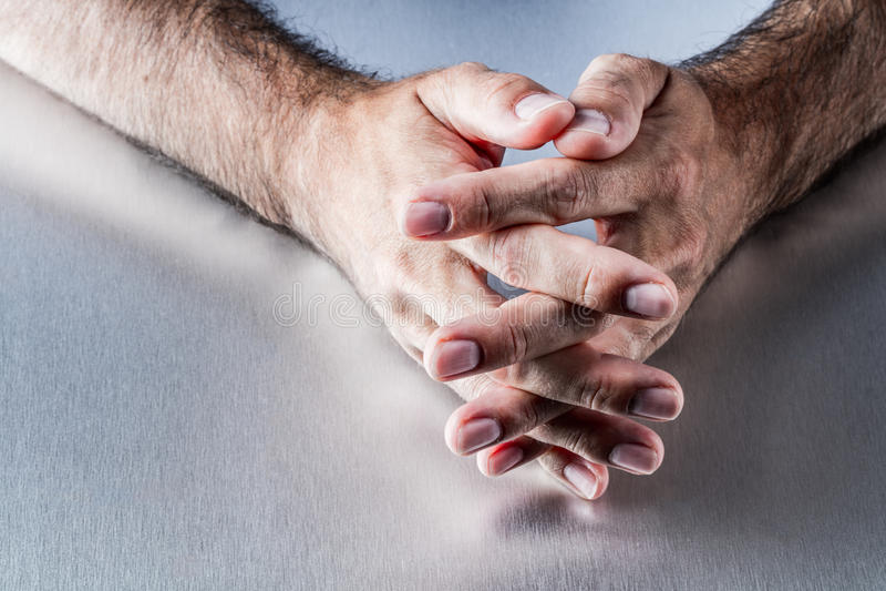 Anonyma manliga håriga händer som korsar fingrar som väntar eller tänker tillsammans royaltyfri foto
