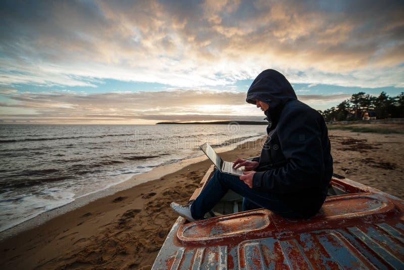 Anonyme dans l'Internet Le programmeur ou le pirate informatique simple travaillant aux îles échouent image stock