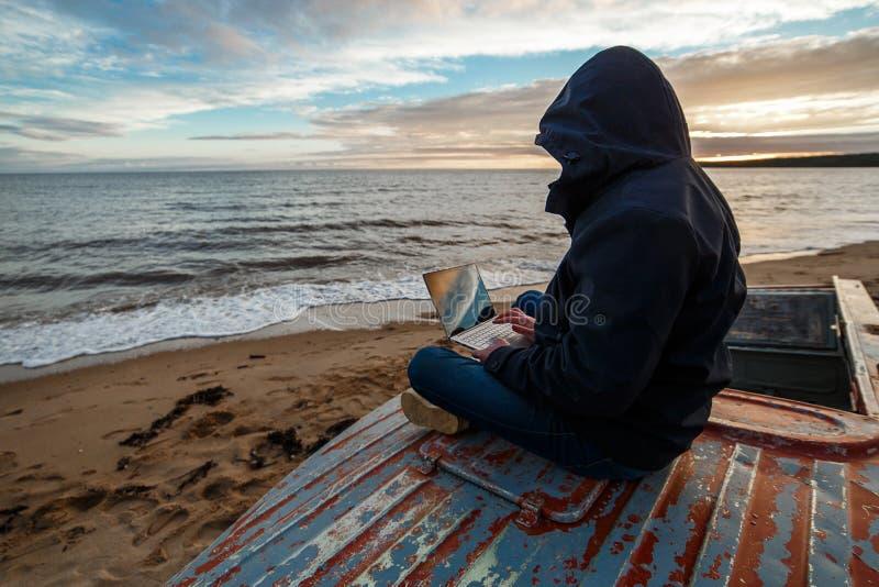 Anonyme dans l'Internet Le programmeur ou le pirate informatique simple travaillant aux îles échouent images libres de droits